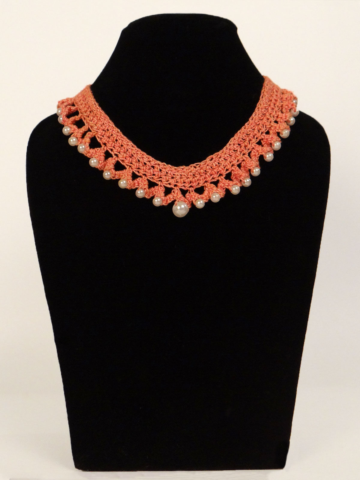 Orange crochet fabric necklace with white pearls.
