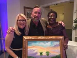 Glen Ryals and his guest Mary Ann Haggerty pictured with their winning auction item and Doretha Hair Truesdell who graciously donated the painting pictured