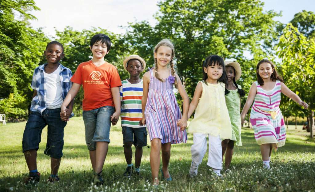 Group of diverse kids having fun together in the park ...