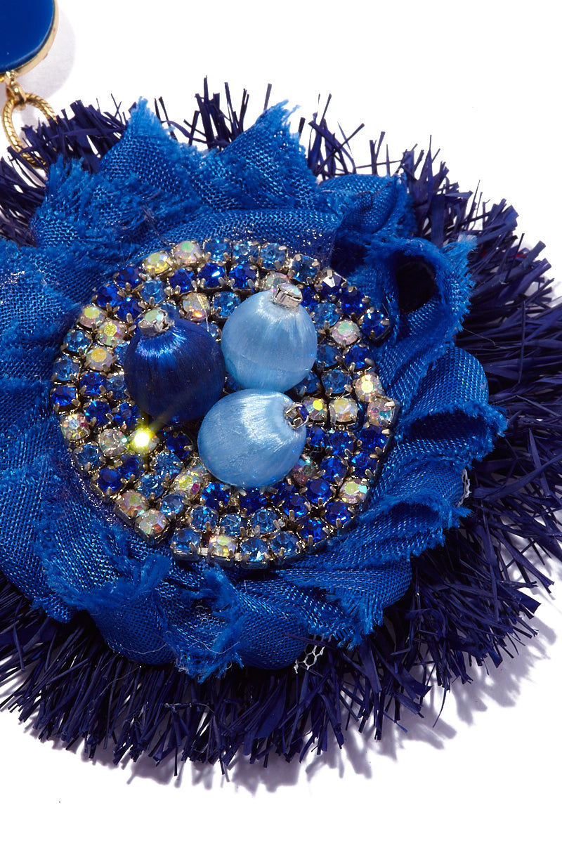 AURORAH Dangle Flower Earrings - Deep Blue Jewelry | Deep Blue| Aurorah Dangle Flower Earrings - Deep Blue Close Up View Natural fiber and textile earrings Crystal and bead embellishments Stud round is .7″ Flower dangle is 3″ Earrings dust or dangle an inch or so above most shoulders Made in the USA