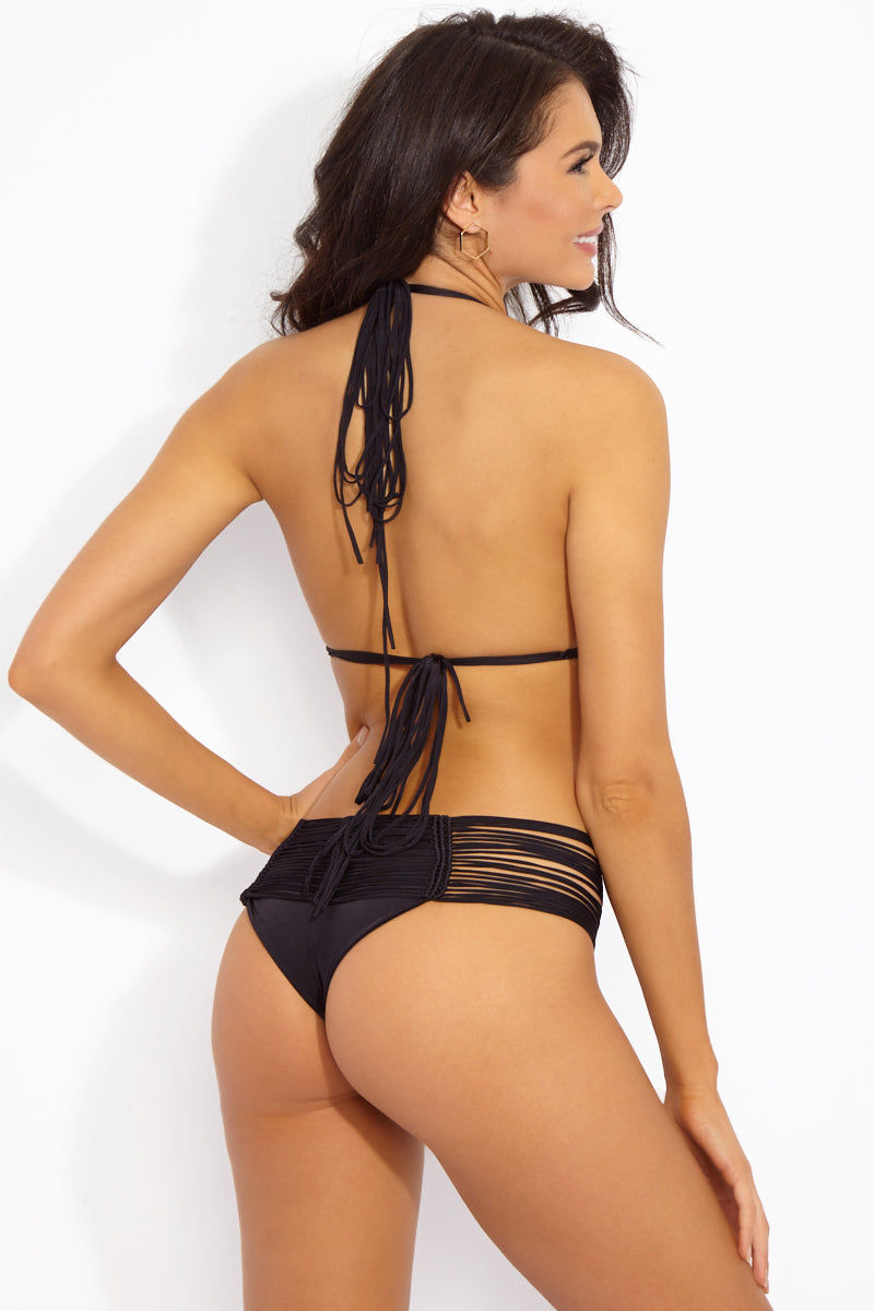 INDAH Fallen Macrame Cheeky Bikini Bottom - Black Bikini Bottom | Black| Indah Fallen Macrame Cheeky Bikini Bottom - Black Mid-rise cheeky black bikini bottom with unique multi-string knot detail. Macrame-inspired cords meet in knotted vertical lines at front and back. Wide multi-strap waistband smoothes your curves and gives the bohemian bikini bottom a sexy finish. Sleek black lining ensures you're fully covered where you need to be under the peek-a-boo strands. Super cheeky Brazilian butt Back View
