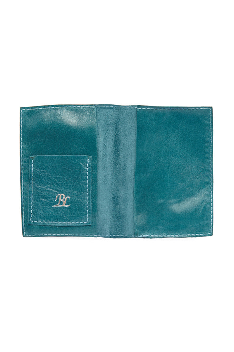 BLYTHE LEONARD Passport Cover - Bermuda Blue Accessories | Bermuda Blue| Blythe Leonard Passport Cover - Bermuda Blue Interior pocket for passport Additional adjacent pocket One Interior card slot patch pocket  Silver embossed lettering  Handmade in the USA Teal color  Genuine leather finish with subtle wrinkling  Pattern may very from picture shown Front View