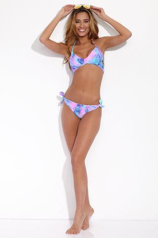 LULI FAMA Laura Reversible Halter Wrap Bikini Top - Palmares Tie Dye Print Bikini Top | Palmares Tie Dye Print | Luli Fama Laura Reversible Halter Wrap Bikini Top - Palmares Tie Dye Print Chic sporty style top in a multicolored pink and blue neon tropical palm print. Deep plunging neckline accentuates your décolletage and fixed triangle cups Flirty and on-trend side cut outs Lace-up strappy back detail Front View