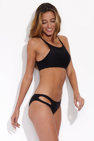 BEACH JOY Sexy Cut Out Bikini Bottom - Licorice Bikini Bottom | Licorice| Beach Joy Sexy Cut Out Bikini Bottom - Licorice. Front Side View. Sexy cut-out bikini bottom in classic black. Sides have double-strap look with front cut-outs. Stretchy material offers moderate rear coverage.