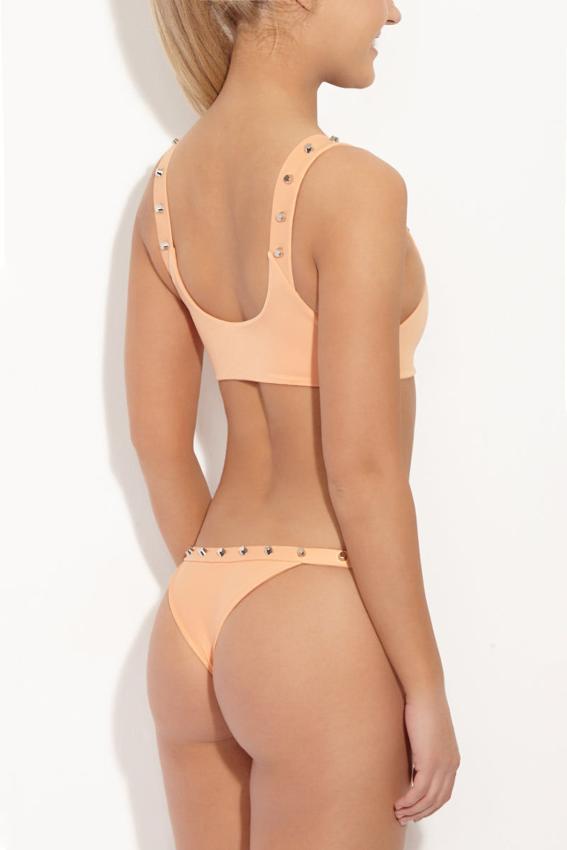 INDAH Mona Studded Bralette Bikini Top - Light Peach Bikini Top | Light Peach| Indah Mona Studded Bralette Bikini Top - Light Peach Playful tank-style pastel peach bikini top with silver studded strap detail. Chunky studs line the straps front and back, giving an edgy balance to the sweet colored bikini top. Scoop neck, wide band, and thick fixed shoulder straps lift and support your bust. Sporty stretch pull-over style stays put all day and doubles as a sports bra for yoga class. Back View