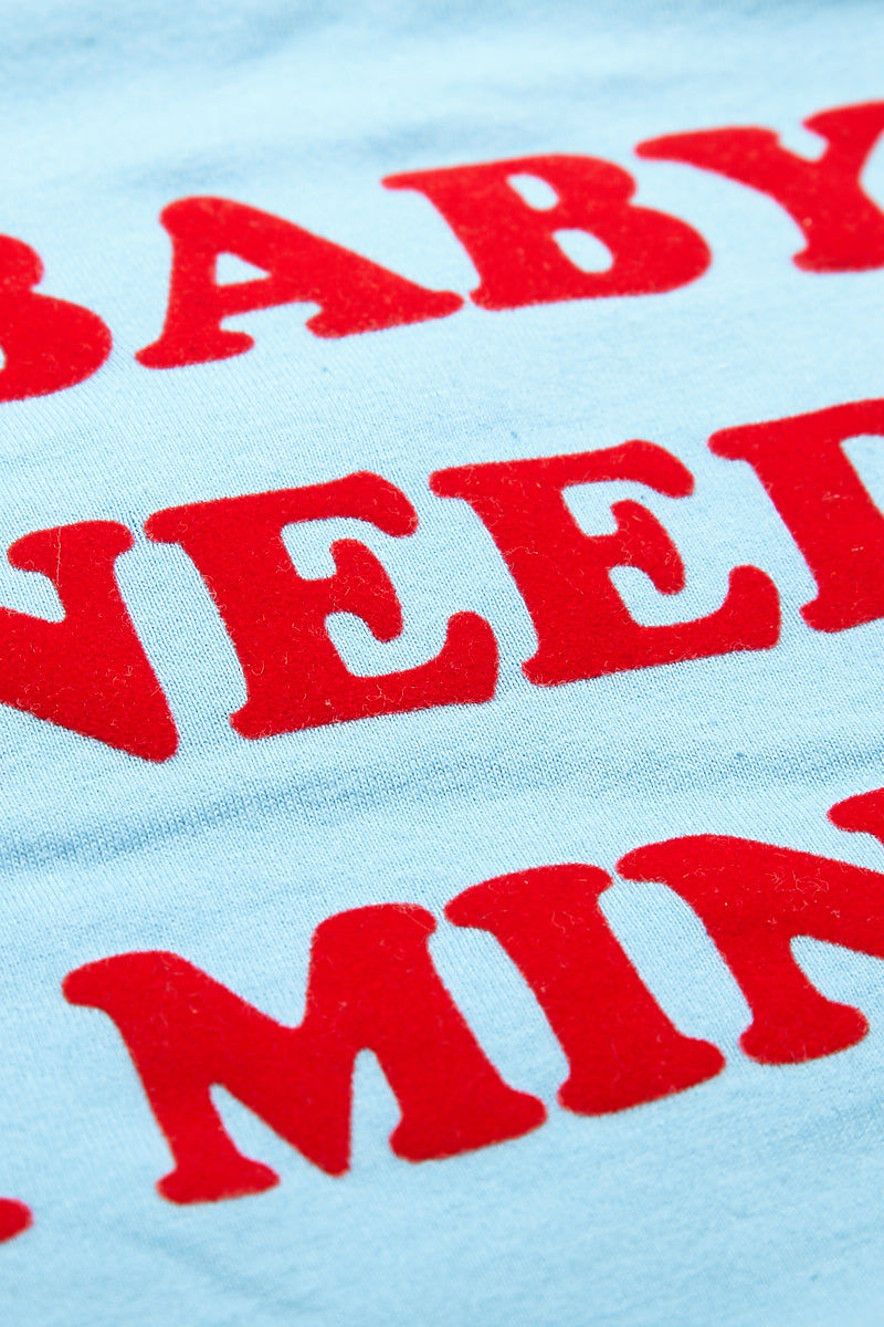 TOP KNOT GOODS Baby Needs A Minute Tee - Baby Blue Top   Baby Blue  Top Knot Goods Baby Needs A Minute Tee - Baby Blue Ultimate Mood T-shirt  Flocked text has a raised, fuzzy feel in red Unisex sizing  Ultra soft  Subtle stretch jersey 100% combed ring-spun cotton  Front View