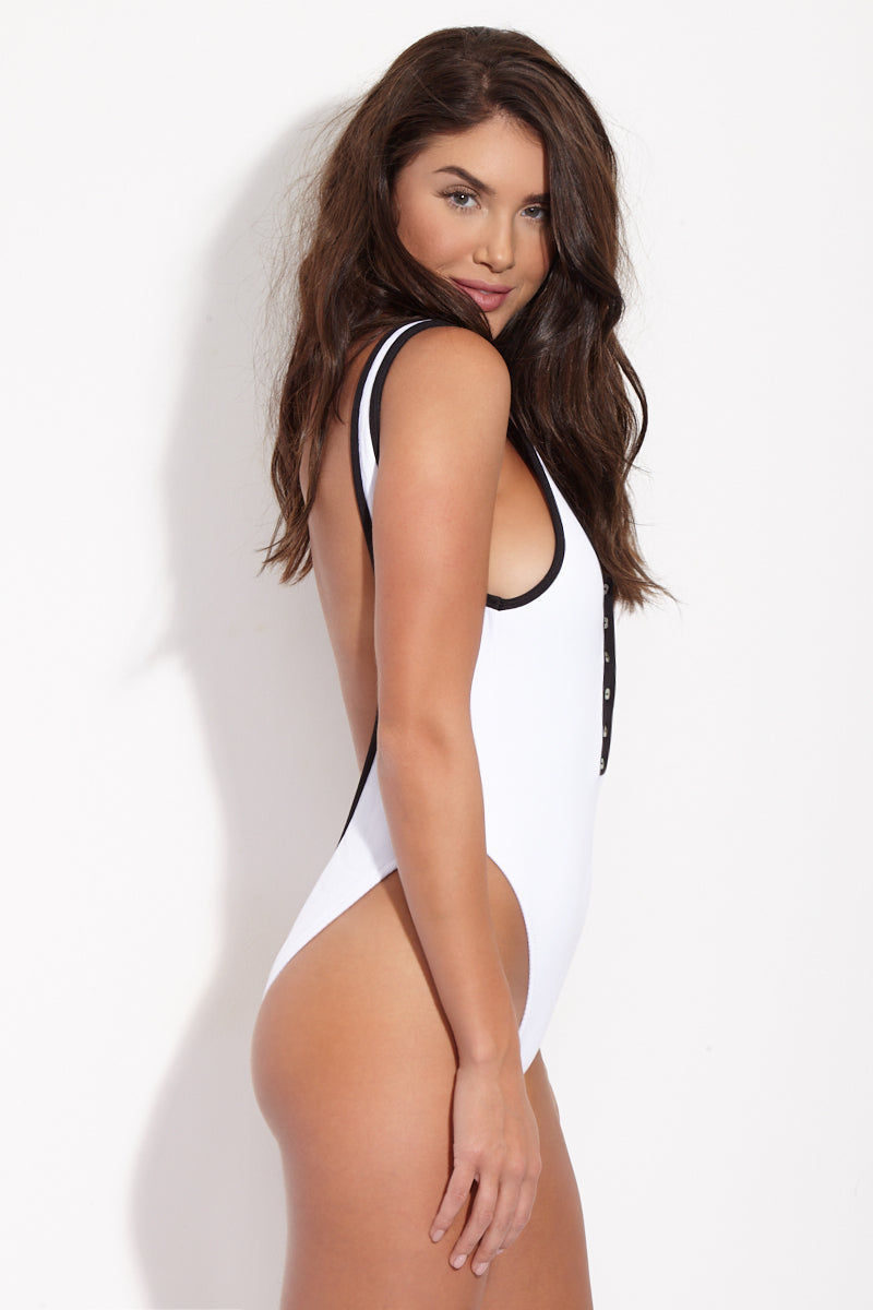 BEACH BUNNY Presley Sporty Button Up One Piece Swimsuit - White & Black One Piece | White & Black| Beach Bunny Presley Sporty Button Up One Piece Swimsuit - White & Black  Button-up white one piece swimsuit with black contrast detailing. Working snap buttons allow you to decide how much cleavage you reveal. Black and white color-blocked detail is super mod and perfectly on-trend. Scoop neck and super deep scoop back flatter your figure and show off your curves. High-cut leg with moderate rear coverage elongates your torso without being too cheeky. Side View