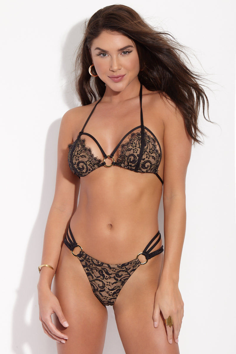 BEACH BUNNY Gunpowder Lace High Cut Bikini Bottom - Black Bikini Bottom | Black| Beach Bunny  Gunpowder Lace High Cut Bikini Bottom - Black Strappy lingerie-inspired high-cut bikini bottom in sexy black lace. Sultry lace front is fully lined in nude fabric so the see-through look is just an illusion. Luxe gold loops at each hip connect the triple-strap sidebands that wrap around back and secure with third gold loop at center. Ruched scrunch back panel accentuates and flatters your booty while providing moderate rear coverage. Front View