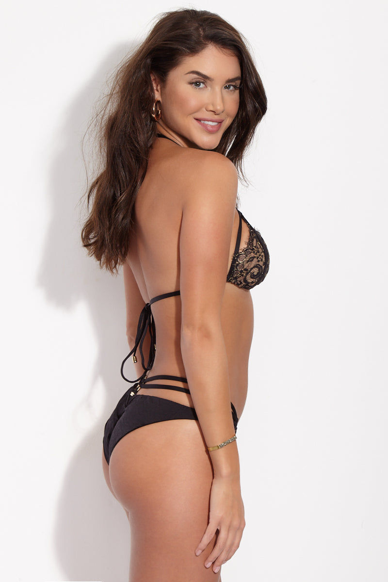 BEACH BUNNY Gunpowder Lace High Cut Bikini Bottom - Black Bikini Bottom | Black| Beach Bunny  Gunpowder Lace High Cut Bikini Bottom - Black Strappy lingerie-inspired high-cut bikini bottom in sexy black lace. Sultry lace front is fully lined in nude fabric so the see-through look is just an illusion. Luxe gold loops at each hip connect the triple-strap sidebands that wrap around back and secure with third gold loop at center. Ruched scrunch back panel accentuates and flatters your booty while providing moderate rear coverage. Side View