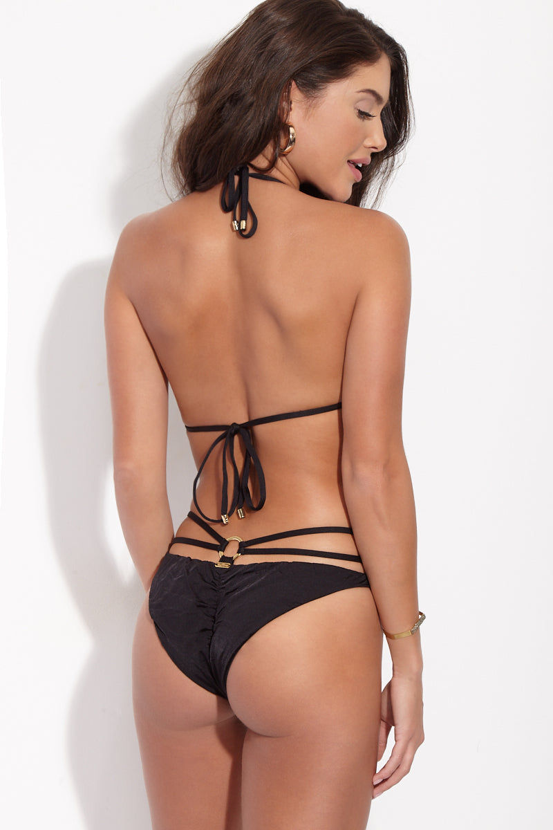 BEACH BUNNY Gunpowder Lace High Cut Bikini Bottom - Black Bikini Bottom | Black| Beach Bunny  Gunpowder Lace High Cut Bikini Bottom - Black. Back View. Strappy lingerie-inspired high-cut bikini bottom in sexy black lace. Sultry lace front is fully lined in nude fabric so the see-through look is just an illusion. Luxe gold loops at each hip connect the triple-strap sidebands that wrap around back and secure with third gold loop at center. Ruched scrunch back panel accentuates and flatters your booty while providing moderate rear coverage.