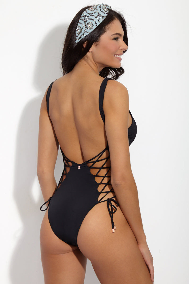 RADIO FIJI Virage Side Lace Up One Piece - Obsidian One Piece | Obsidian | Radio Fiji Virage Side Lace Up One Piece - Obsidian. Back View. Scoop Neckline. Thick shoulder straps. Lace up back sides. Scoop back. High cut leg. Cheeky coverage