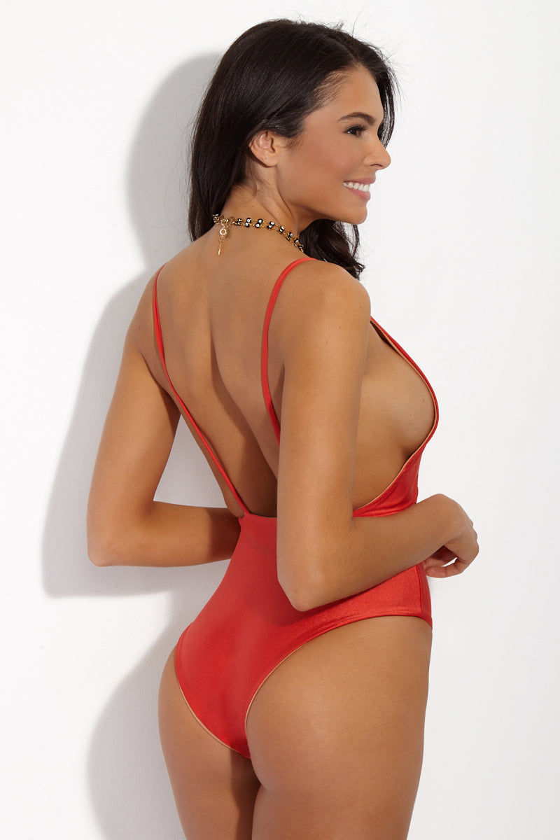 SIE SWIM Zoe Plunging Neckline One Piece - Sunset One Piece | Sunset| SIE SWIM Zoe Plunging Neckline One Piece - Sunset. Back View. Plunging red one piece swimsuit with 90's style high-cut leg. Saturated orange-red sunset color radiates warmth from afar. Deep open back and plunging neckline show off your sideboob.