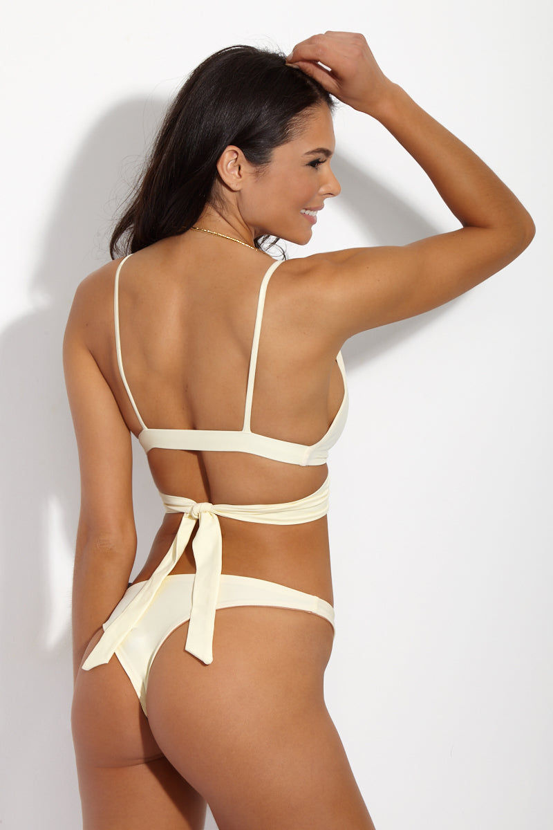 SIE SWIM Kyle Twist Wrap Bikini Top - Ivory Bikini Top | Ivory| SIE SWIM Kyle Twist Wrap Bikini Top - Ivory. Back View. Plunging twist-front wrap bikini top in luxe ivory fabric with a rose gold lining. Fabric twists at front and around back for a flattering high-fashion wrap effect. Spaghetti straps and wide band add just the right amount of support to the bikini top. Seamless design offers ultimate comfort. Wear as a crop top with your favorite high-waisted pants for a chic street look. Complete the bikini with the SIE SWIM Ivory Madison Bikini Bottom