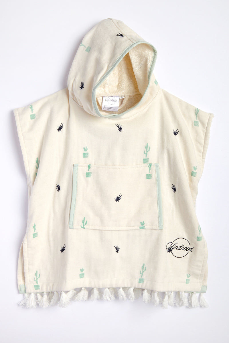 KINDHOOD Sonora Poncho (Kids) - Cream Plant Print Kids Resort | Cream Plant Print| Kindhood Sonora Poncho (Kids) - Cream Plant Print Cozy, eco-friendly hooded poncho for children ages 2 to 8. Soft cream fabric sprinkled with navy blue leaves and seafoam green plants and piping. Trimmed with fluffy cream tassels at bottom. Front View