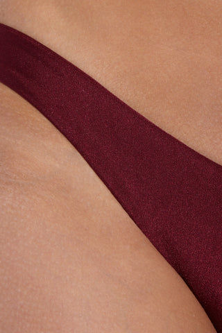 SARA CRISTINA Ola Low Rise Cheeky  Bikini Bottom - Burgundy Red Bikini Bottom | Burgundy Red| Sara Cristina Ola Low Rise Cheeky  Bikini Bottom - Burgundy Red Elegant, luxurious burgundy bikini bottom with a little sheen. Low-rise cut. Cheeky to moderate coverage. Gold-plated logo at back. Front View