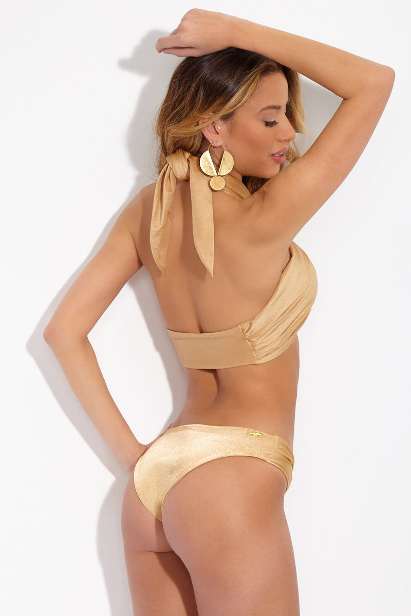 SARA CRISTINA Gold Wrap Bikini Bottom Bikini Bottom | Gold| Sara Cristina Gold Wrap Bikini Bottom Luxurious pale gold bikini bottom with a little sheen. Loop detailing on the sides creates small cut outs. Low-rise cut. Cheeky to moderate coverage.