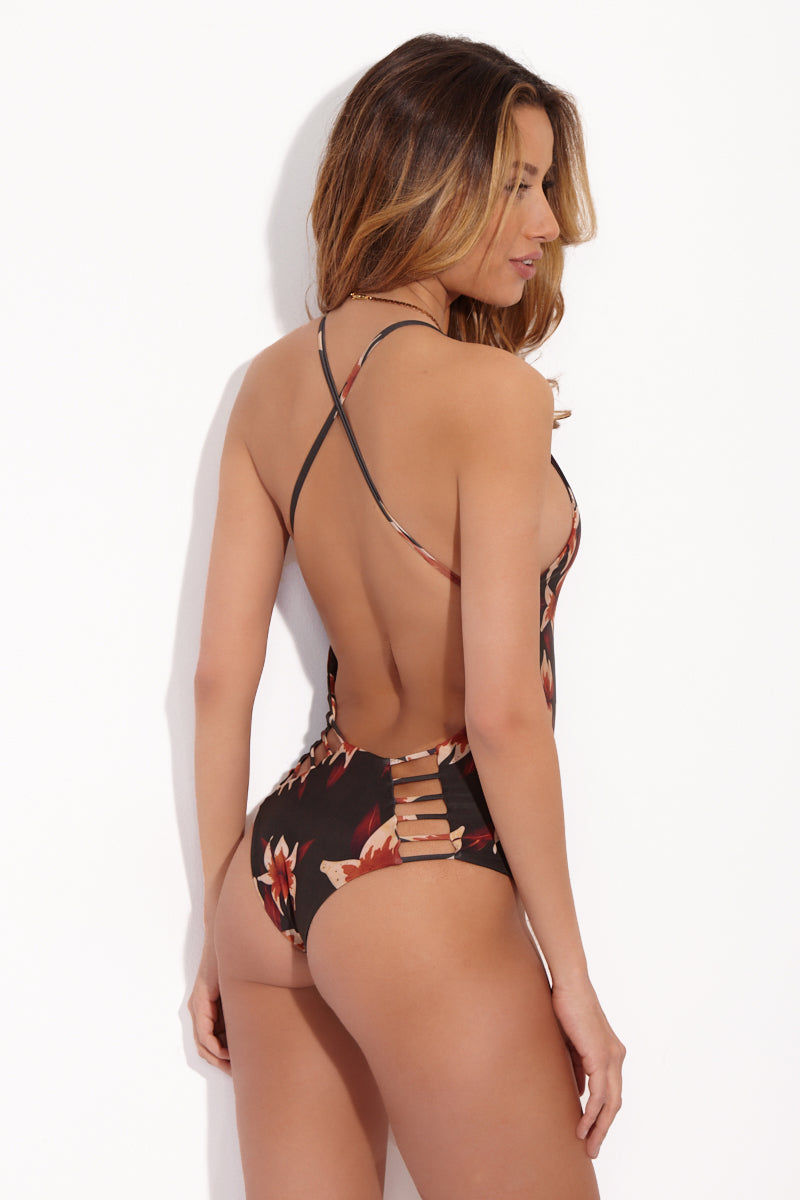 STONE FOX SWIM Palma Plunging Open Back One Piece Swimsuit - Natural Mystic Print One Piece | Natural Mystic Print| Stone Fox Swim Palma Floral Backside Cutouts One Piece - Natural Mystic Print Deep-v plunging neckline one piece in a deep floral palma print. Criss cross back straps. Low scoop back and ladder strappy detail on the bottom. Cheeky coverage.