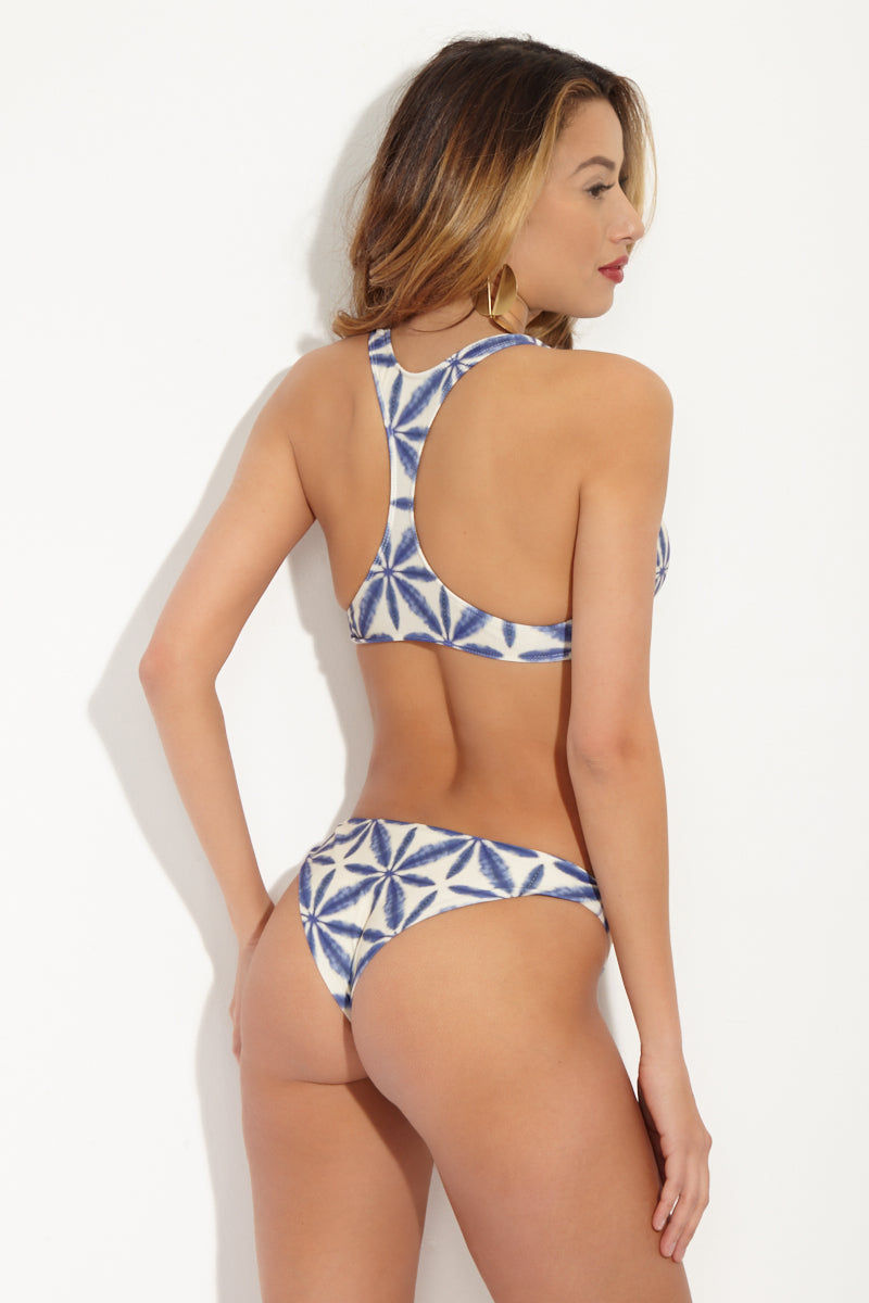 STONE FOX SWIM Loni Sporty T Back Bikini Top - Ocean Blue Batik Print Bikini Top | Ocean Blue Batik Print| Stone Fox Swim Loni Sporty T Back Bikini Top - Ocean Blue Batik Print Ultra-flattering scoop neckline frames your décolletage and shows some skin. Wide, fixed shoulder criss-cross shoulder straps sit comfortably on your shoulders. Slim racerback design flatters your shoulder blades and provides extra bust support. Back View
