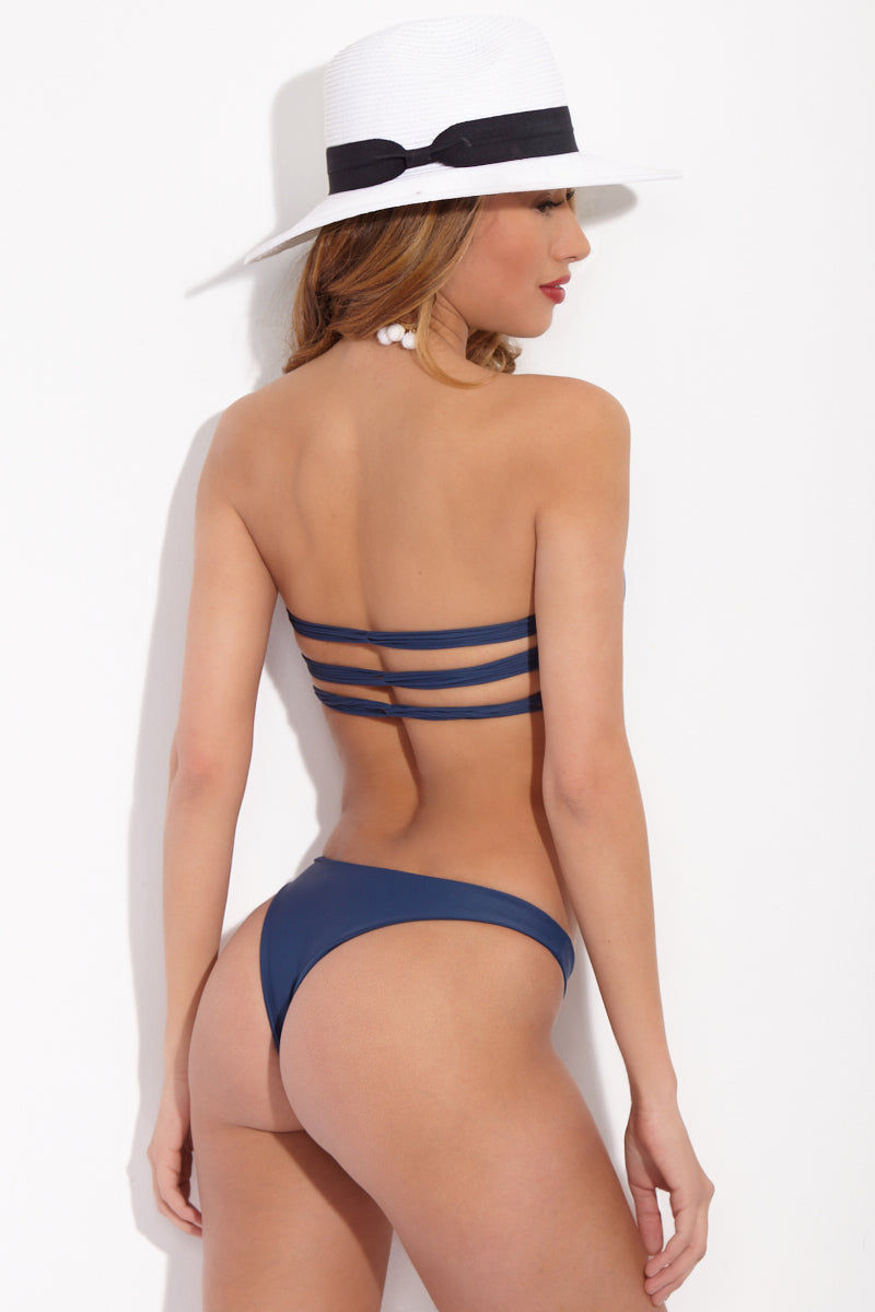 MIKOH Lahaina Low Rise Seamless Bikini Bottom - Drop Off Blue Bikini Bottom | Drop Off Blue|Mikoh Lahaina Low Rise Seamless Bikini Bottom - Drop Off Blue. Features: Low rise skimpy minimalist bikini bottom. Wide side straps can be hiked up at the hips. Seamless and hardware free. Double lined fabric. View: On model, full back view.