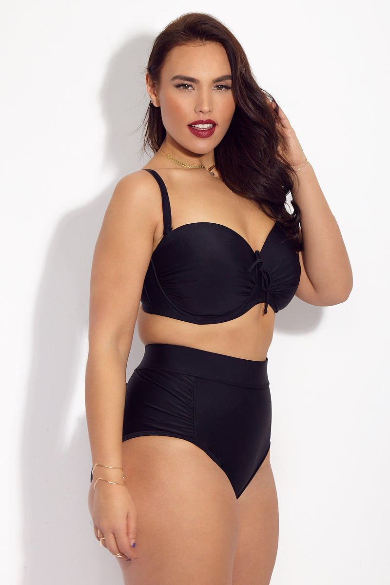 SKYE+ Waverly High Waist Bikini Bottom (Curves) - Black Bikini Bottom   Black  SKYE+ Waverly High Waist Bikini Bottom (Curves) - Black. Features: Classic black full coverage high waisted plus size bikini bottom. Ruched panels on hips for added shaping. Wide ruched details at the hips for shaping. Tummy control panels visually slim torso. High waist fit provides full coverage while still looking stylish. Gold toned label at mid-back below seam.