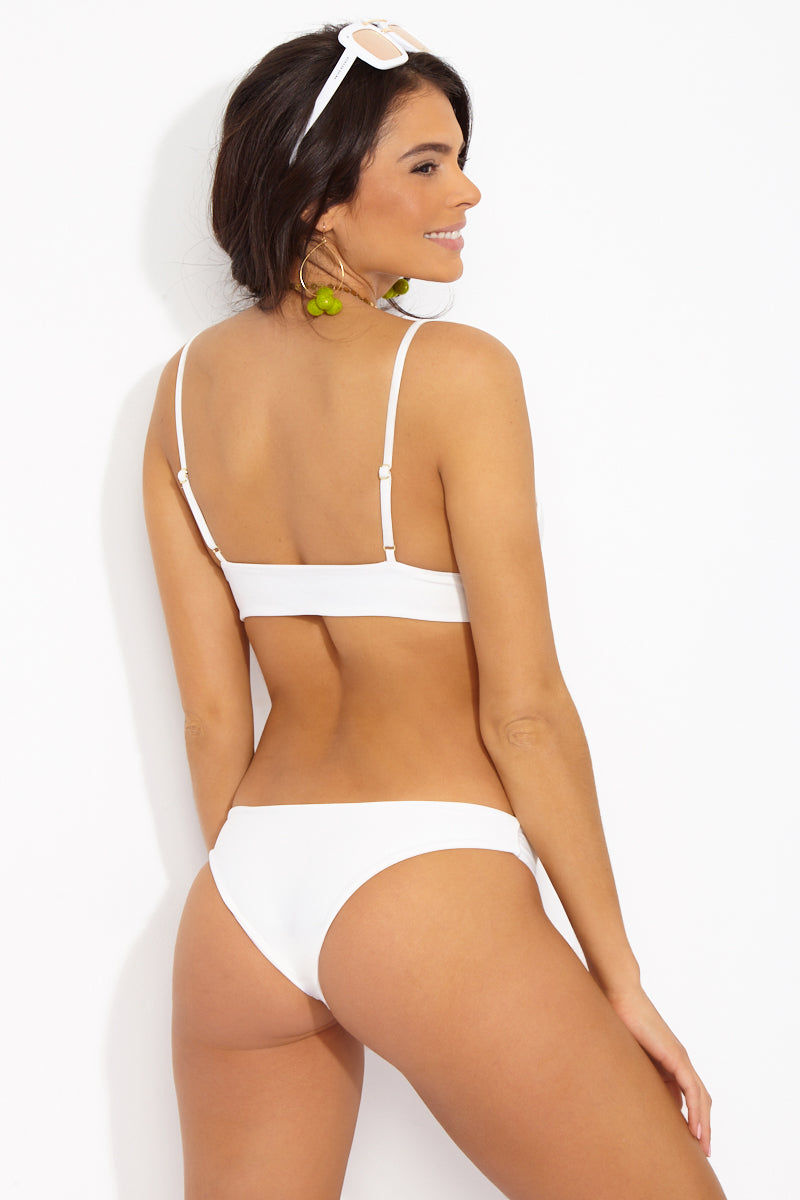 TORI PRAVER Chiara Cheeky Bikini Bottom - Ceramic White Bikini Bottom | Ceramic White| Tori Praver Chiara Cheeky Bikini Bottom - Ceramic White White low-rise bikini bottom with cheeky coverage. Hipster front cut shows off your curves while still providing moderate coverage. Wide side bands smooth and flatter your figure without digging into your skin. Back View