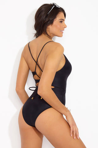 VIX SWIMWEAR Twisted Lace Up Back One Piece Swimsuit - Black One Piece | Black| Vix Swimwear Twisted Lace Up Back One Piece Swimsuit - Black Deep v-neck one piece swimsuit in classic black. Diagonal seams at the front define your waistline and create the appearance of an hourglass figure. Thin straps cascade over your shoulders and meet at the back in a crisscross design. Corset-style adjustable lace-up detailing Back View
