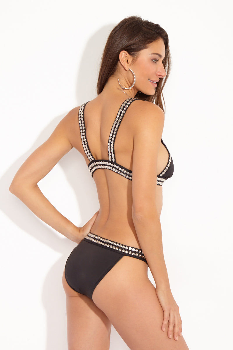 NORMA KAMALI Stud Banded Bikini Bottom - Black Bikini Bottom | Black| Norma Kamali Stud Banded Bikini Bottom - Black Back View . Skimpy banded bikini bottom trimmed with two rows of flat silver studs. The daring design offers minimal front and rear coverage. Wide studded waistband adds an edgy, badass finish to the bikini bottom. Norma Kamali's studded swimwear is an iconic fashion status symbol, coveted by celebrities, bloggers, and editors. Complete the skimpy bikini with the Norma Kamali Stud Banded Triangle Bikini Top - Black.