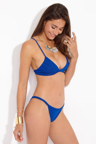 FELLA Otis Triangle Cut Cheeky Bikini Bottom - Royal Blue Bikini Bottom | Royal Blue| Otis Bottom Front Side View Classic True blue fixed triangle bikini bottom ideal of tanning. Thin binded sides minimize tan lines so you get the perfect glow. Triangle-cut front and cheeky rear cut provide minimal coverage without being to skimpy. Fully lined high-quality Italian Lycra fabric in saturated primary blue color is the perfect way to rock the primary color blocking trend.
