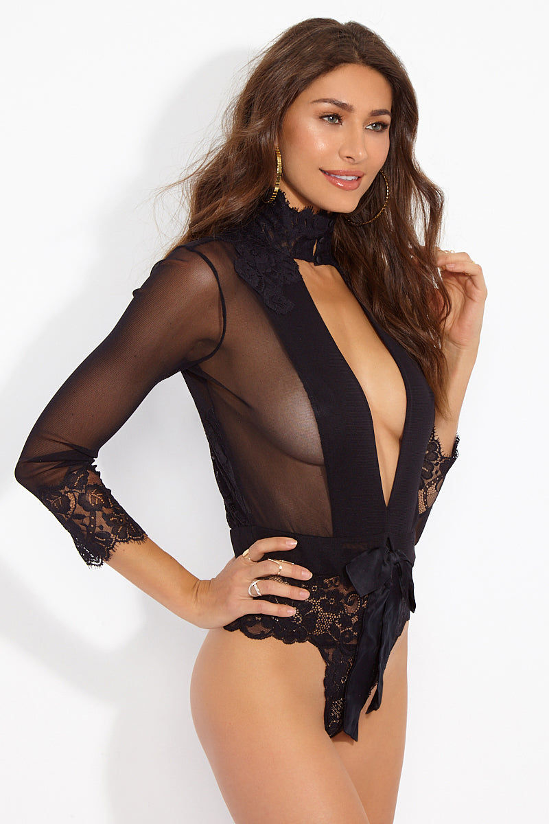 WE ARE HAH Multi-Way Take HAH Bow Thong Bodysuit - Noir Bodysuit | Noir| Hot As Hell Reversible Take Hah Bow Bodysuit - Noir Side View Can Be Worn Front or Back Long Sleeves Turtleneck with Button Closure  Satin Sash Cinches  Tie Bow Front Or Back  Cheeky Lace Brief  Fully Lined