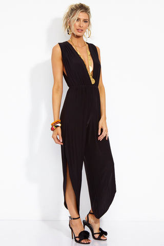 WE ARE HAH Michele HAH Belle Capri Jumpsuit - Noir Jumpsuit | Noir| Hot As Hell Michele Hah Bell Jumpsuit - Noir Side View  Deep V Front & Back  Back Tie Closure  Essential Deep Pockets  Elastic Waist Loose Fitting Pant Legs Side Slits  NAUGHTY KNIT: 90% Polyester, 10% Spandex