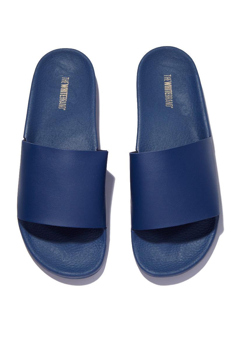 THE WHITEBRAND Minimal Slides (Men's) - Navy Sandals | Navy|Minimal Slides (Men's) - Navy. Features:  Men's flat slide sandal in navy blue Made of PVC Navy blue vamp Synthetic exterior Textile interior 3cm high ergonomic Lightweight sole