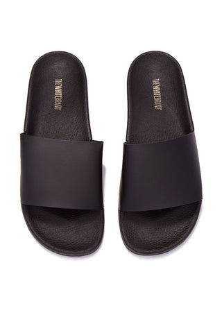 THE WHITEBRAND Minimal Slides (Men's) - Black Mens Sandals | Black|WHITEBRAND  Minimal Slides (Men's) - Black. OutSide Sole View.  Features:  Men's flat slide sandal in black Made of PVC Black vamp Synthetic exterior Textile interior 3cm high ergonomic Lightweight sole