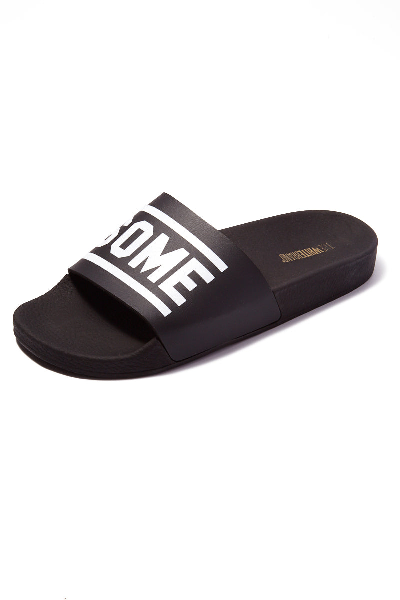 THE WHITEBRAND Awesome Minimal Slides (Men's) - Black Mens Sandals | Black|WHITEBRAND Awesome Minimal Slides (Men's)- Black. Features: Men's flat slide sandal in black Made of PVC Black mesh vamp Horizontal stripes are attached and the word AWESOME in black rubber 3cm high ergonomic lightweight sole