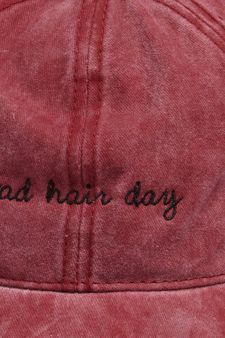 "DAVID & YOUNG Bad Hair Day Slogan Baseball Cap - Burgundy Hat | | David & Young Bad Hair Day Slogan Baseball Cap - Burgundy close up view cursive black Bad Hair Day Washed-out burgundy baseball cap with ""bad hair day"" embroidery in white."