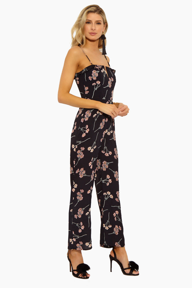 FLYNN SKYE Parker Jumpsuit - Black Cherry Blossom Jumpsuit | Black Cherry Blossom| Flynn Skye Parker Jumpsuit - Black Cherry Blossom Side View Cropped Pant Jumpsuit V Neckline  Adjustable Spaghetti Straps  Top Ruffle Detail  Bustier Back Closure Empire Waist  Open Back Detail