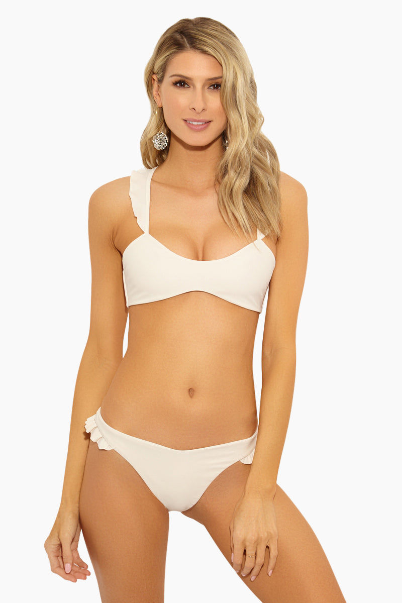 GILLIA Sonia Ruffle Bikini Bottom - Cream Bikini Bottom | Cream| GILLIA Sonia Ruffle Bikini Bottom - Cream STYLE:  Low-rise V-cut skimpy bikini bottom in a luxurious cream shade. Allover minimal coverage is ideal for tanning as it leaves less noticeable tan lines. Ultra romantic ruffle detail on the side straps balance out the sexier aspects of the suit. Brazilian rear cut shows off your curves while providing skimpy coverage.    CARE:  Hand wash in cold water with gentle detergent and lay flat to air dry. 80% nylon, 20% spandex. Front View