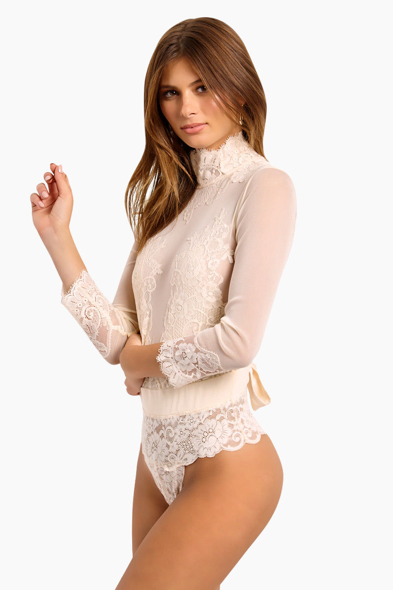 WE ARE HAH Multi-Way Take HAH Bow Thong Bodysuit - La Crème Bodysuit   La Crème  Hot As Hell Reversible Take Hah Bow Bodysuit - La Crème Can Be Worn Front or Back Long Sleeves Turtleneck with Button Closure  Satin Sash Cinches  Tie Bow Front Or Back  Cheeky Lace Brief  Fully Lined  Side View