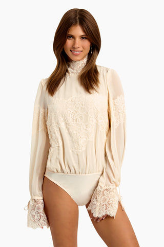 WE ARE HAH Queen 4 A Day Bodysuit - La Crème Bodysuit | La Crème| Hot As Hell Queen 4 A Day Bodysuit - La Crème Features:  Lace & Chiffon Bodysuit  Lace Turtle Neck Oversized Sleeves  Ties At The Wrist  Comfortable Knit Brief Front View