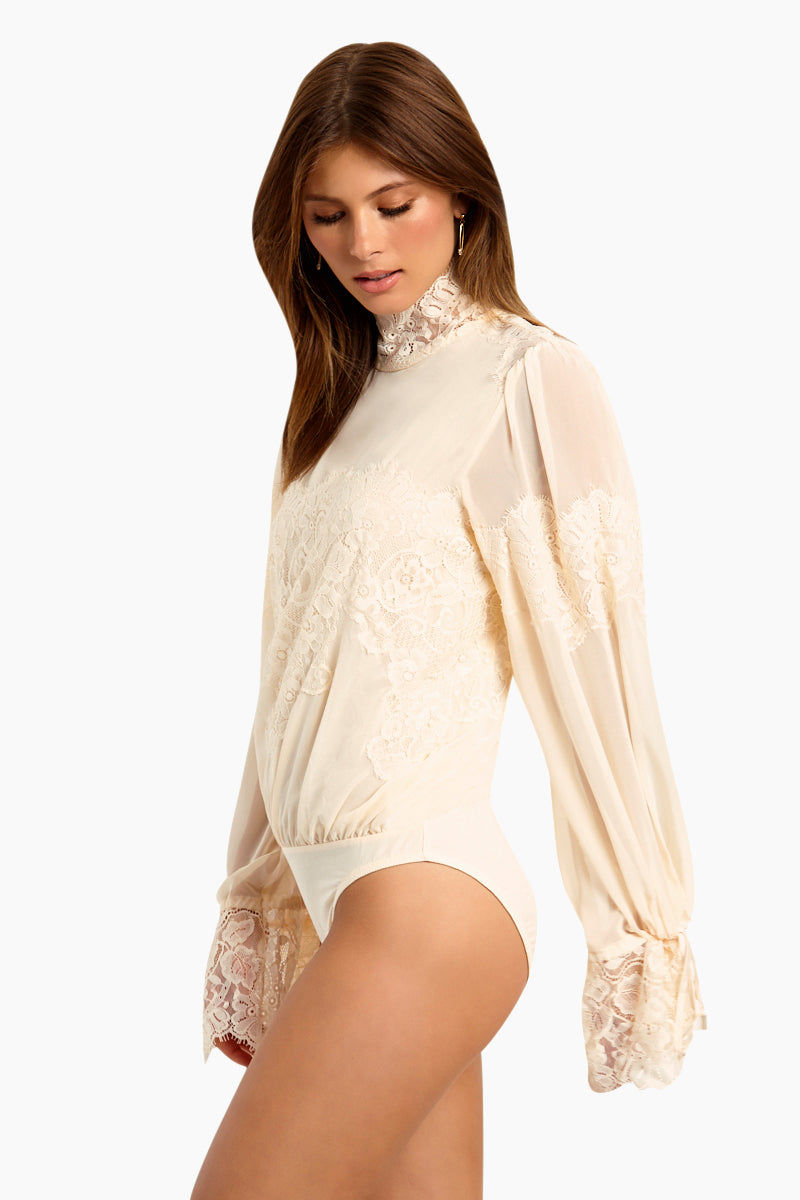 WE ARE HAH Queen 4 A Day Bodysuit - La Crème Bodysuit | La Crème| Hot As Hell Queen 4 A Day Bodysuit - La Crème Features:  Lace & Chiffon Bodysuit  Lace Turtle Neck Oversized Sleeves  Ties At The Wrist  Comfortable Knit Brief Side View