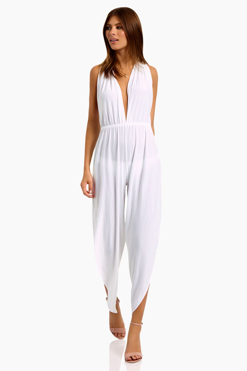 WE ARE HAH Michele HAH Belle Capri Jumpsuit - Blanc Jumpsuit | Blanc| Hot As Hell Michele Hah Bell Jumpsuit - Blanc Features:  Deep V Front & Back  Back Tie Closure  Essential Deep Pockets  Elastic Waist Loose Fitting Pant Legs Side Slits  NAUGHTY KNIT: 90% Polyester, 10% Spandex   Care Machine wash cold, hang to dry Front View