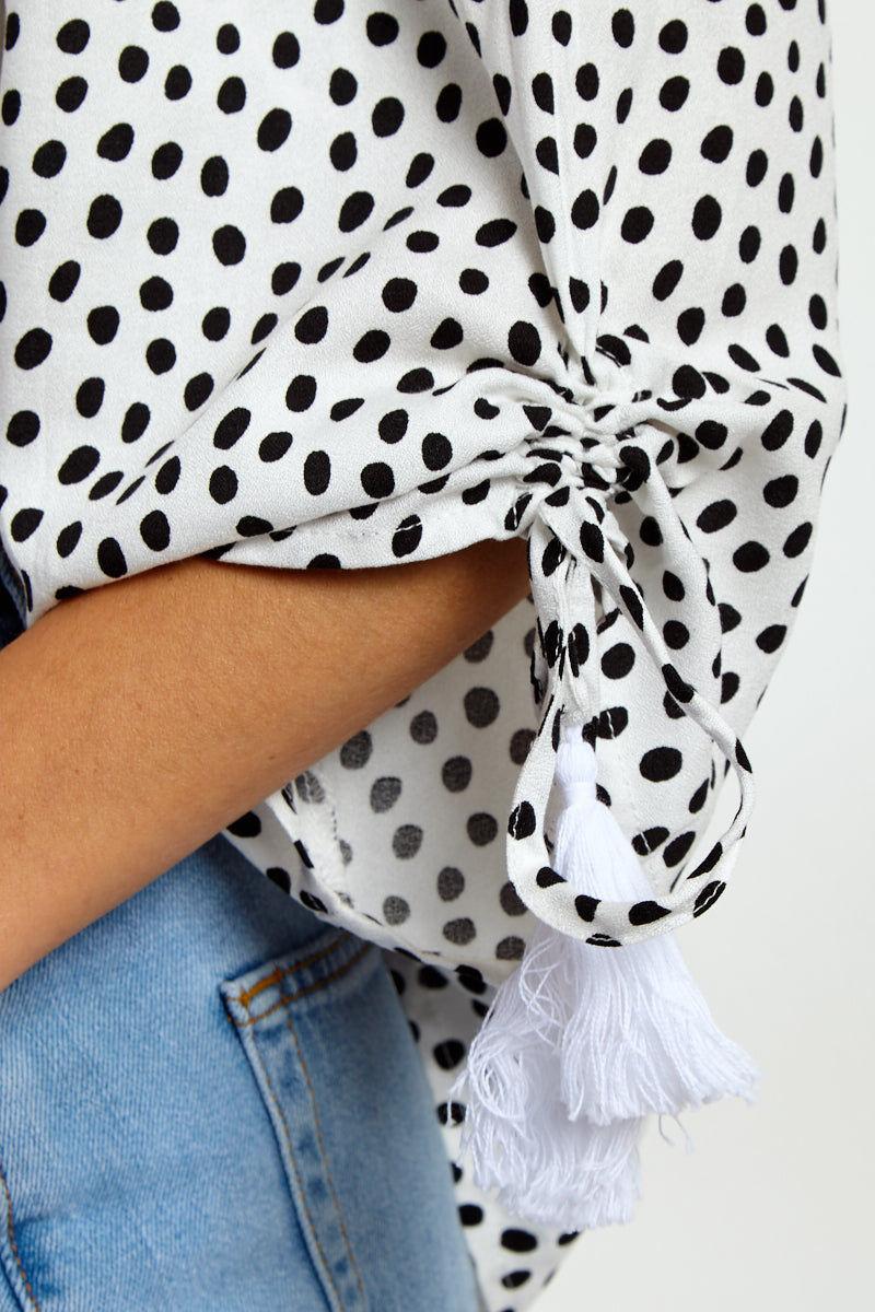 MINKPINK Tilly Off Shoulder Top - Black & White Polka Dot Top | Black & White Polka Dot| Black & White Polka Dot| MinkPink Tilly Off Shoulder Top - Black & White Polka Dot Off Shoulder Top  Cinched Sleeve Detail  Tassel Ends on Strings Close Up View