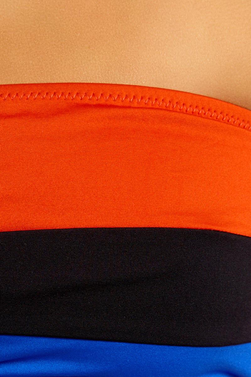 NESSI BYRD Erica Off Shoulder Bandeau Bikini Top - Orange Color Block Bikini Top | Orange Color Block| Nessi Byrd Erica Off Shoulder Bandeau Bikini Top - Orange Color Block Features:  Bandeau Bikini Top  Off Shoulder Sleeves Color Block with Orange, Black, & Blue  Back Clasp Closure Close up view