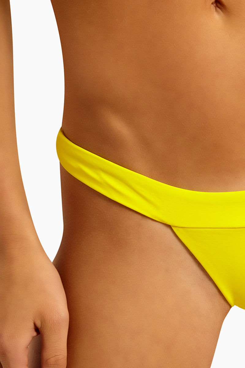 BEACH BUNNY London Skimpy Bottom - Bright Yellow Bikini Bottom   Bright Yellow  Beach Bunny London Skimpy Bottom - Bright Yellow Cheeky banded bikini bottom in playful bright yellow color. Low-rise cut and thin sidebands provide sexy skimpy coverage and make the bikini bottom ideal for tanning. Smooth back panel shows off your natural curves in the cheeky cut. Easy stretch pull-on style free of ties and hardware keeps you ultra-comfortable all day. Detail view