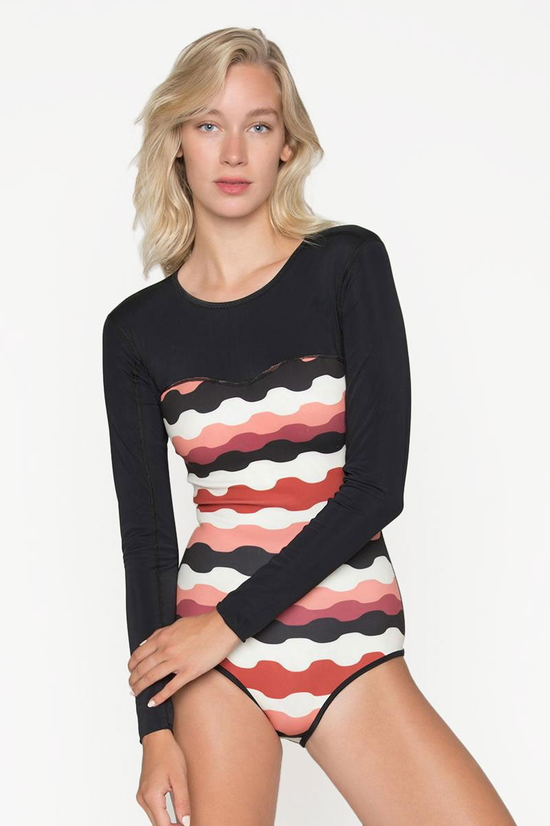 SEEA Floripa Reversible Long Sleeve Rashguard Bodysuit - Buzios Abstract Print/Coco Red Wave Stripe Print One Piece   Buzios/Coco Print  Seea Floripa Reversible Surf Suit - Buzios. Features:  Recycled nylon/spandex sleeves and C-skin fabric body. Fabric rated UPF 30+ - 50+ Original Buzios and Coco prints. Long sleeves and fully covered back for sun protection. Underarm side panel to reduce chafing while paddling. Flattering, curved pattern lines. Classic cut bottom. Fully lined, however no shelf bra or padding is included. For more support, we suggest wearing a bikini top underneath. Made in sunny California Front View