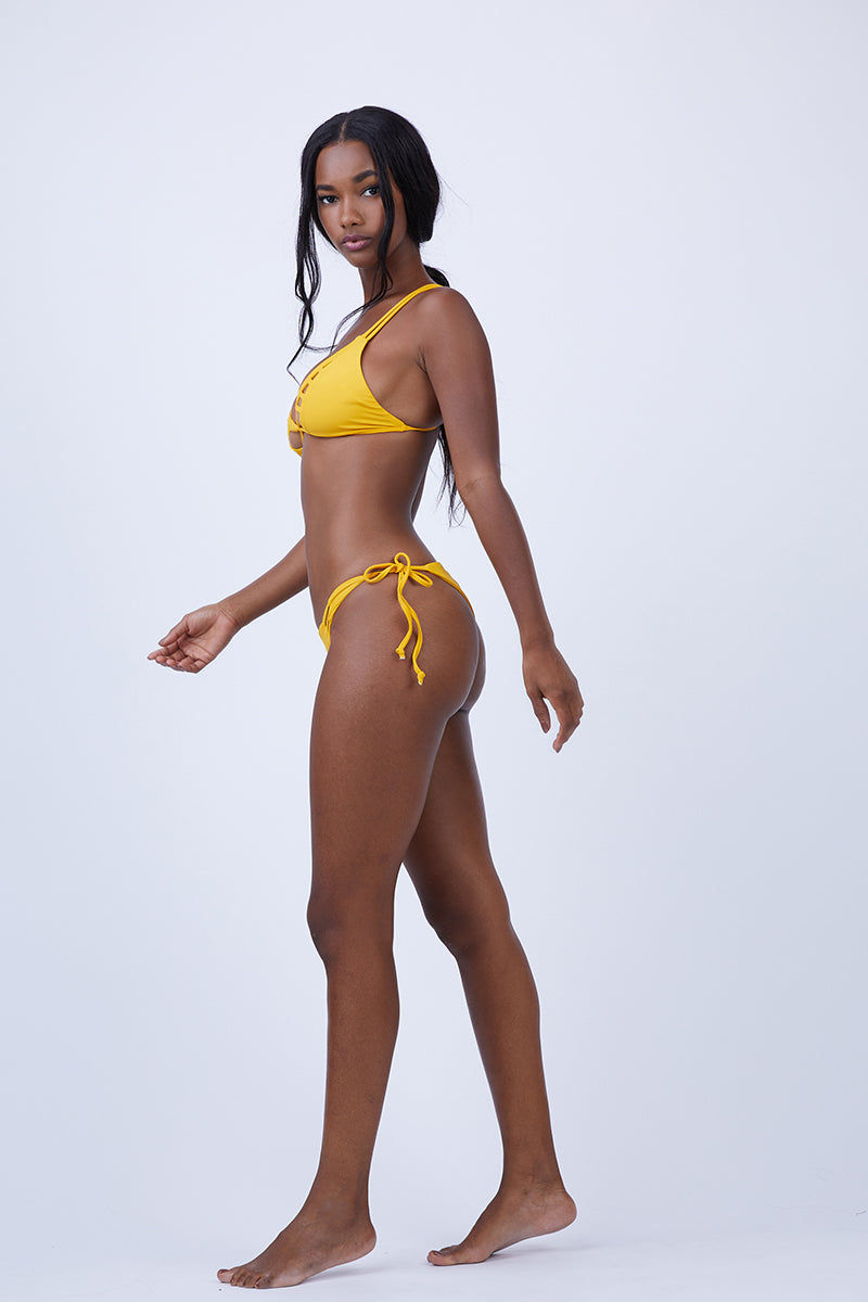 KEVA J Jasmine Cut Out Bikini Bottom - Mustard Bikini Bottom |  Mustard| Keva J Jasmine Cut Out Bikini Bottom - Mustard. Features:  Strappy detail in the front Ties at both sides Minimal coverage in back 80% Nylon, 20% Spandex Double Lined Made In The USA Front View