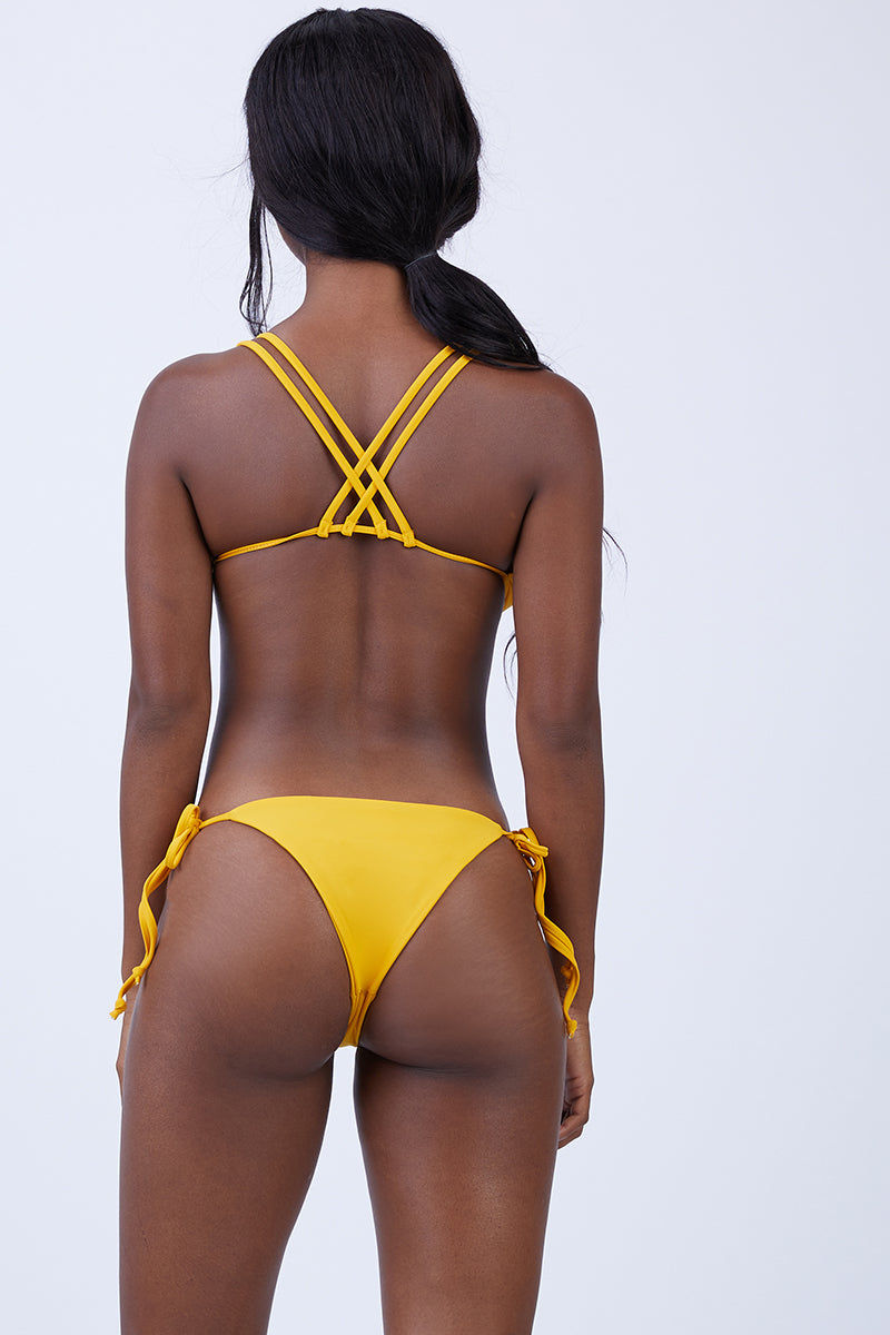 KEVA J Jasmine Cut Out Bikini Bottom - Mustard Bikini Bottom |  Mustard| Keva J Jasmine Cut Out Bikini Bottom - Mustard. Features:  Strappy detail in the front Ties at both sides Minimal coverage in back 80% Nylon, 20% Spandex Double Lined Made In The USA Back View