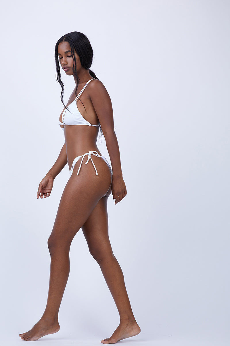 KEVA J Jasmine Cut Out Bikini Bottom - White Bikini Bottom | White| Keva J Jasmine Cut Out Bikini Bottom - White. Features:  Strappy detail in the front Ties at both sides Minimal coverage in back 80% Nylon, 20% Spandex Double Lined Made In The USA Front View