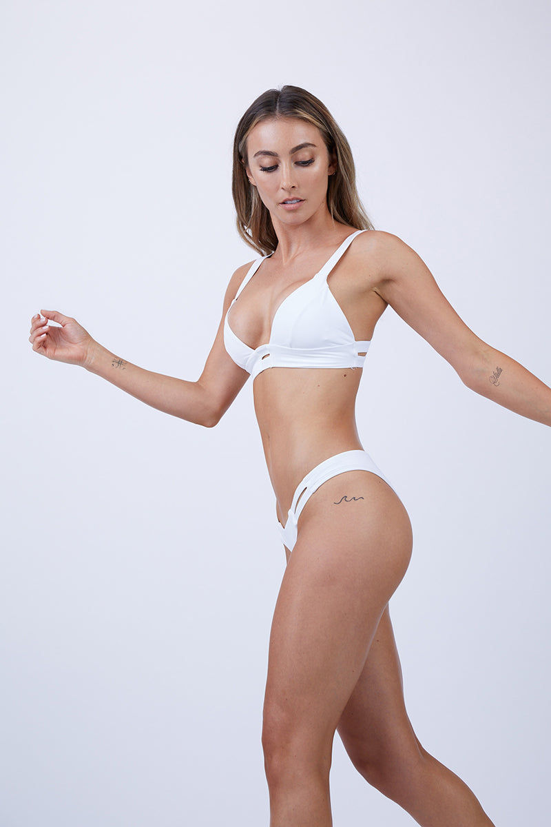 VITAMIN A Neutra Bralette Top - White Bikini Top | White| Vitamin A Neutra Bralette Top - White  Comfortable pullover Bralette-style bikini top Thick shoulder straps Double elastic underbust bands Double back straps Cut out at the center of the bust Diagonal seams on each bust cup Smooth, clean finish Side View