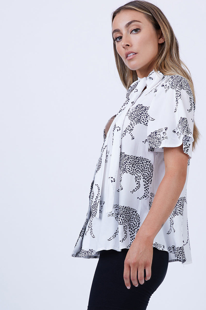 LENNI Mars Short Sleeve Blouse - Monocat Top | Monocat| Lenni Mars Short Sleeve Blouse - Monocat. Side View. Features:  Short sleeve button down front Pussy bow neck Content:  Made from 100% hand-drawn and printed rayon fabric