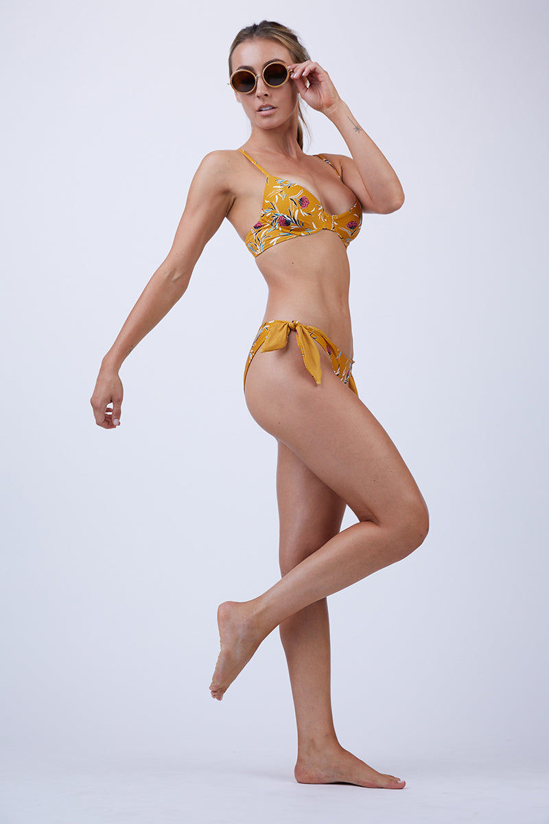 BEACH RIOT Camilla Underwire Bikini Top - Yellow Bikini Top | Yellow| Beach Riot Camilla Underwire Bikini Top - Yellow Yellow bikini top with red floral pattern  Underwire  Adjustable spaghetti straps  Back hook closure Polyester/Spandex blend Hand wash cold; lay flat to dry Made in the USA Side View